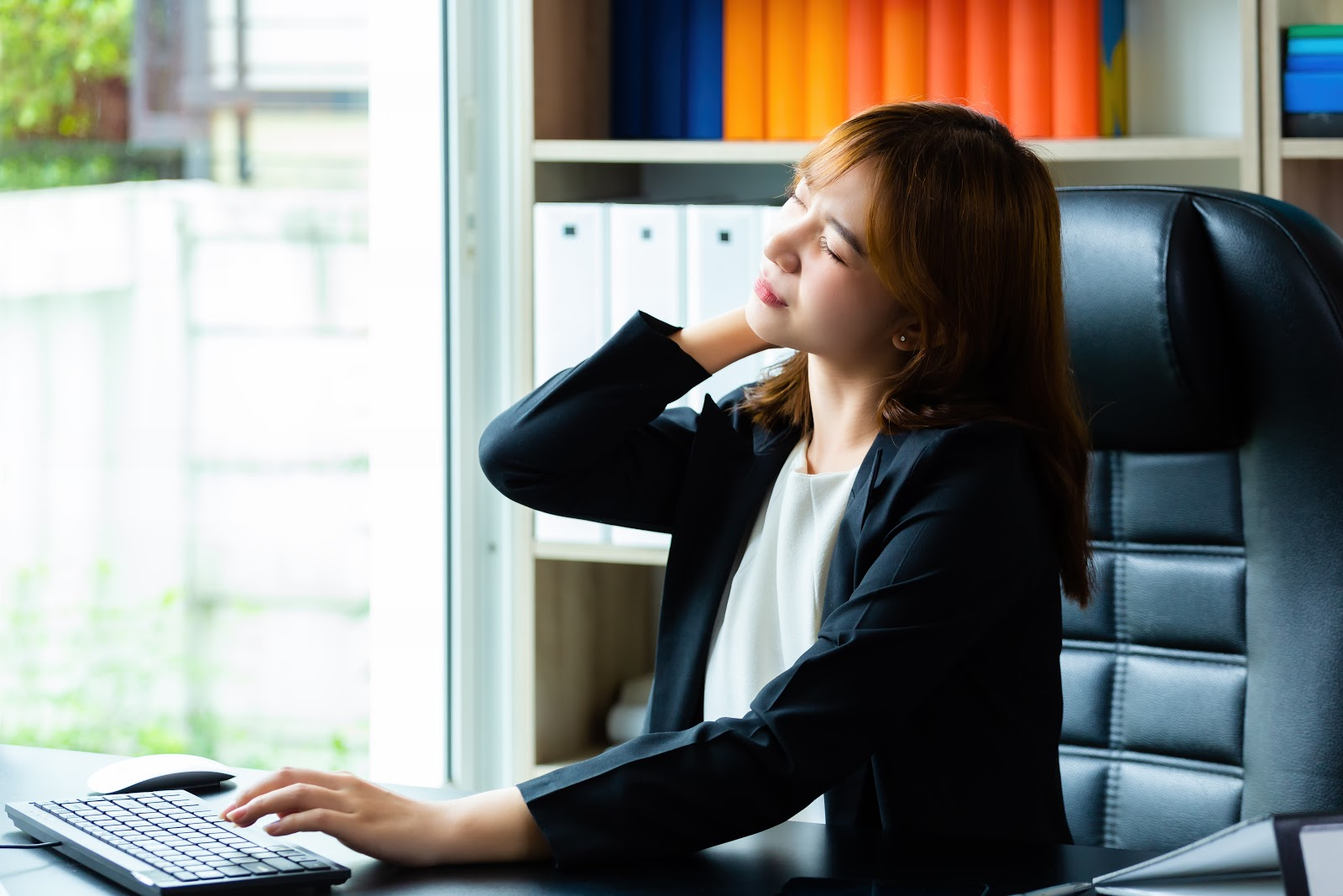 Young working woman has neck pain and tired because work hard in the office